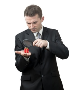 Businessman looking at a small present with a magnifying glass