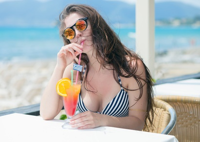 Woman with cocktail in the beach bar during tropical vacation